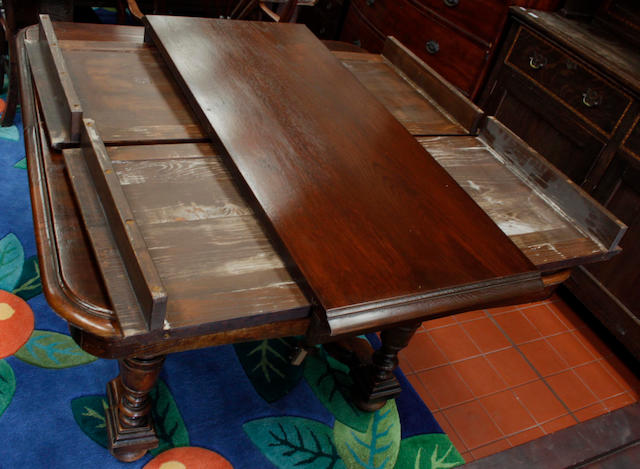 A late Victorian walnut and oak extending dining table,