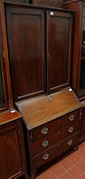 An early 19th Century oak bureau,with matched cabinet top, enclosed by a pair of panelled doors, 84cm wide. (2)