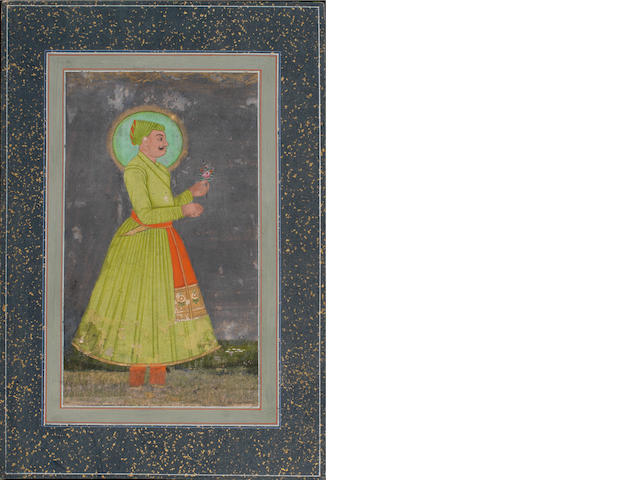 A prince in green facing right holding a flower Rajasthan, 19th Century