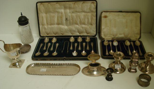 A cased set of eleven silver Old English shell pattern teaspoons and sugar tongs, Mappin & Webb, Sheffield 1915, and the following silver: cased set of six teaspoons and sugar tongs, George III style helmet shape cream jug, 1915, pair of dwarf candlesticks, mounted cut glass castor, pepperette in early 18th Century style, oval capstan shape inkwell, A & J Zimmermann, Birmingham 1914, early 18th Century style pen tray, Levi & Salaman, Birmingham 1909, napkin ring, miniature trophy, eight items of George IV and later silver flatware and cutlery also a small circular Japanese metalware dish.