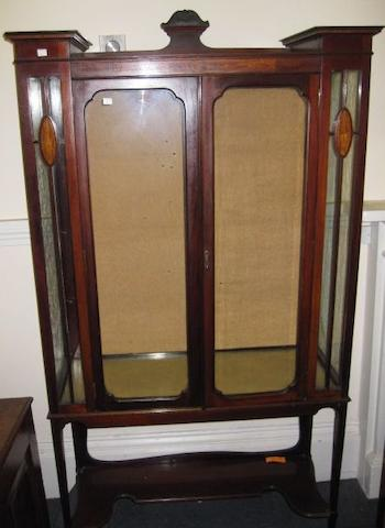 An Edwardian inlaid mahogany display cabinet, the shaped back over glazed doors and inlaid side panels enclosing shelves on square tapered legs united by a shaped undertier, 100cm.