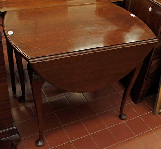 A mahogany oval drop flap table