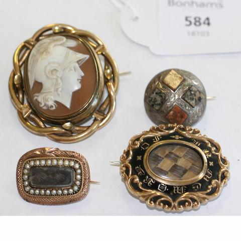 A 19th Century engraved and pebble set boss brooch, a carved shell cameo brooch locket in rolled gold openwork frame, an early Victorian hair set enamel mourning brooch and a Georgian hair set brooch in serpent frame. (4)