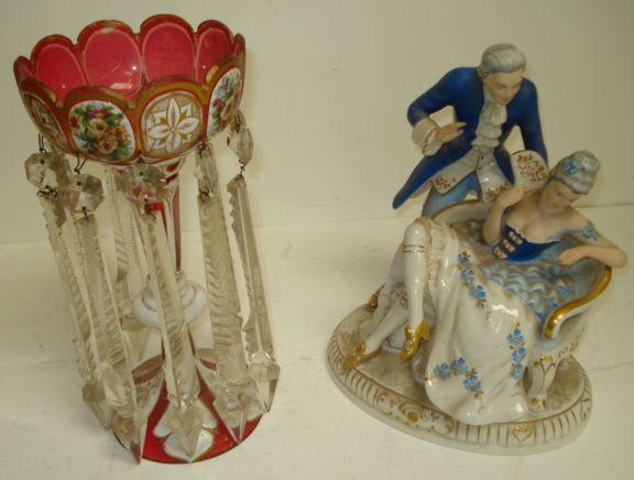 A 19th Century Bohemian ruby glass lustre, white cased, gilt and floral painted hung with cut spike shape drops, and a Royal Dux figure group modelled as a dandy and his lady seated on a canape, impressed, printed and raised marks. (2)