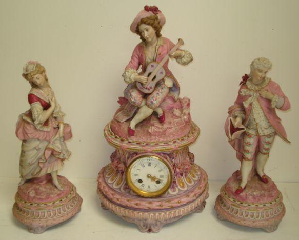 A late 19th Century French coloured bisque clock garniture, the 8 day movement striking on a bell in a columnar case surmounted by a seated musician, the side pieces in the form of a gallant and his lady, predominately in pink, the clock 50cm high, the side pieces 38cm. (3)