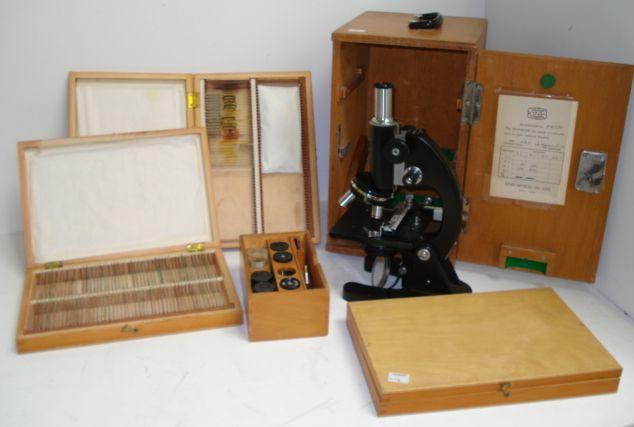 A black enamelled compound monocular microscope, by Ernst Leitz Wetzlar, No 336567, with rack and pinion focusing and triple nosepiece, on a 'Y' shaped base, in fitted wooden carrying case and two others similar, one by Beck, No 36055, grey enamelled, the other by Kine, Tokyo, No 756123, 19 cases of microscope slides and various accessories.