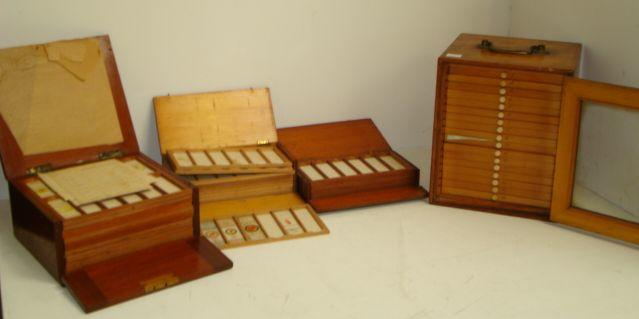 A Victorian stained pine microscope slide cabinet, fitted with 17 drawers containing a collection of slides, enclosed by a glazed panel door, brass carrying handle, 25cm, a mahogany example, the hinged top and fall front enclosing twelve trays of glass microscope slides and two smaller similar, one in mahogany, the other in pine.
