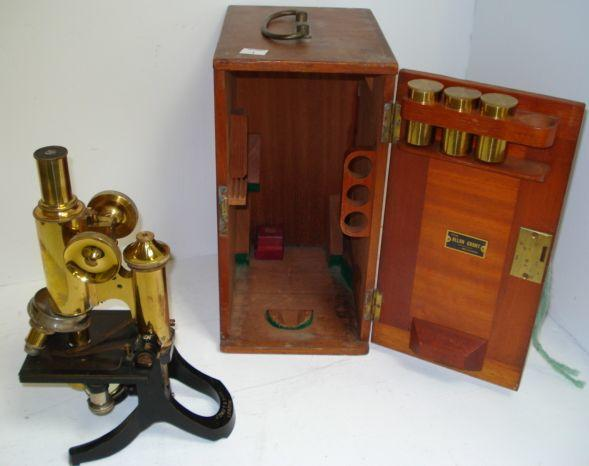 A lacquered brass and enamelled compound monocular microscope, by J Swift & Son, London, No 13399.c, with rack and pinion focusing, triple nosepiece, square mechanical stage and plano concave mirror, in fitted mahogany carrying case with three eyepieces.