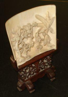 A Chinese carved ivory tusk section panel, pierced and carved with figures gathering fruit, on pierced and carved wood stand, 14.5cm.