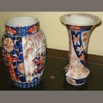 A Japanese Imari decorated panel sided vase, with flared rim, 25cm high, together with a similar vase of reeded baluster form, 24cm high (af).