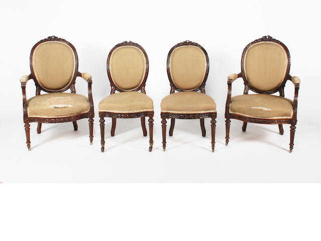 A pair of late 19th century French Louis XVI style foliate carved walnut frame, upholstered fauteuil, and a matching pair of side chairs