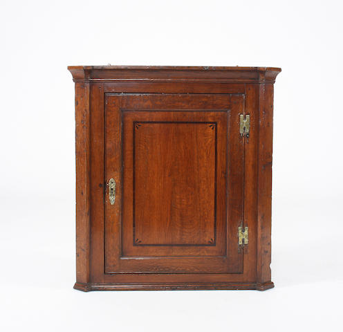 A George III oak and inlaid corner cupboard