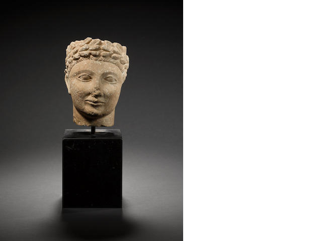 A Cypriot limestone head of a youth with laurel wreath