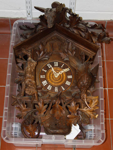 A Black Forest cuckoo clock,the walnut case carved with dead game and oak leaves and with stags head cresting, 66cm high.
