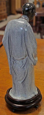 A good quality 20th Century Chinese stoneware figure, standing holding a fly whisk and wearing a crackle glazed silver grey robe and with black lustre, hair and beads, on carved hardwood stand, 22cm high.