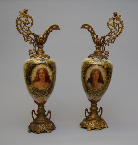 A pair of spelter and milk-glass ewers