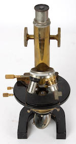 C Reichet-Wein-44557 - a brass japanned finish single pillar microscope, in fitted mahogany box with objective, a lacqured brass single pillar microscope by P & J Beck, London 8464 retailers mark for Brady & Martin Newcastle, with various lenses, in lined mahogany box, a box of various lenses and objectives and two boxes of microscope slides.