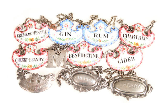 A collection of silver and enamelled decanter labels