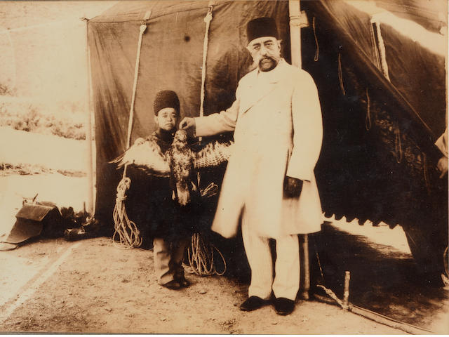 Four photographs of Nasr al-Din Shah Qajar (reg. 1848-96) and Muzaffar al-Din Qajar (reg. 1896-1907), depicting the Shah seated in front of the fabled Peacock Throne in the Gulistan Palace; standing in front of a tent with a falcon; seated in a palace chamber with photographs hanging on the wall behind him; and the Shah and his entourage standing at the entrance to a European building Qajar Persia, probably Tehran, circa 1870-1907(4)
