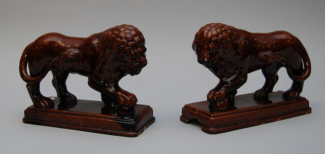A pair of treacle glazed figures of lions