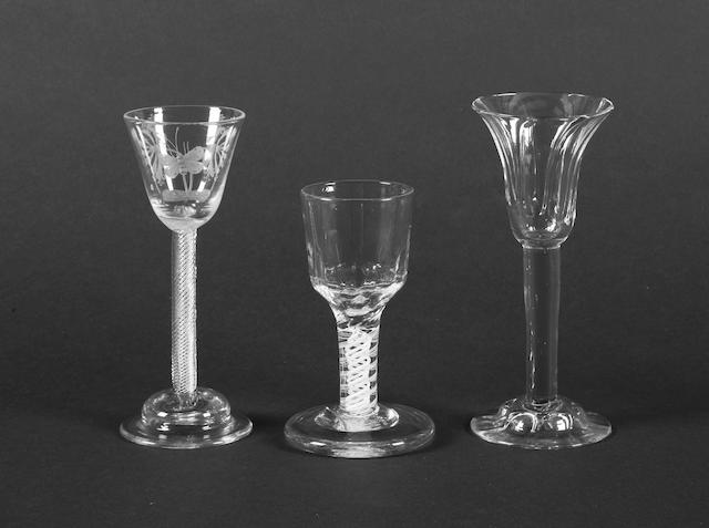 An engraved airtwist wine glass, a plain stem wine glass and an opaque-twist firing glass Late 18th Century.