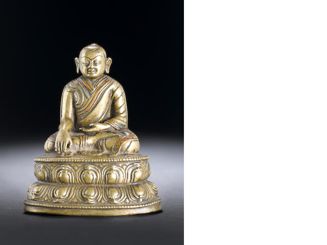 A Tibetan copper-inlaid bronze figure of a lama 16th century