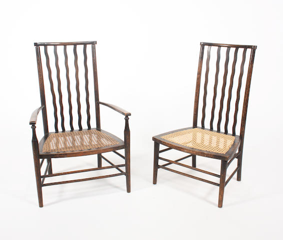 An ebonised beech low elbow chair and matching standard chair attributed to Liberty & Co.