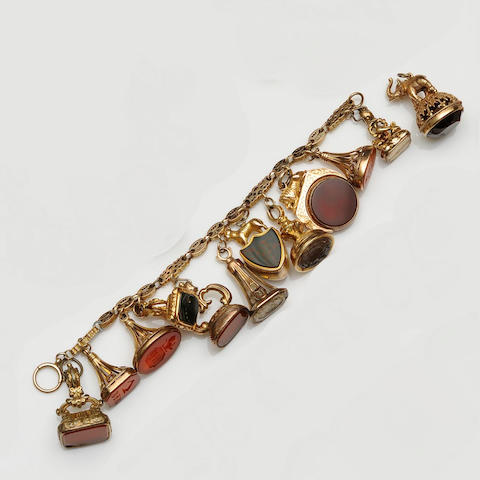 A bracelet suspending assorted 19th century and later gold and gilt metal fob seals