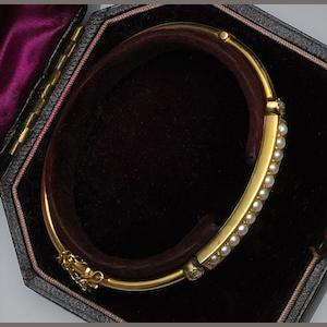A late Victorian 15ct gold half pearl and diamond hinged bangle