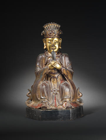 A partially-gilt lacquered bronze figure of a seated official 16th/17th century