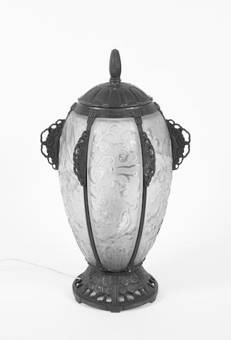 A tall French Art Deco ovoid, patinated, stylised and cast bronze, and frosted/clear glass panelled table lamp