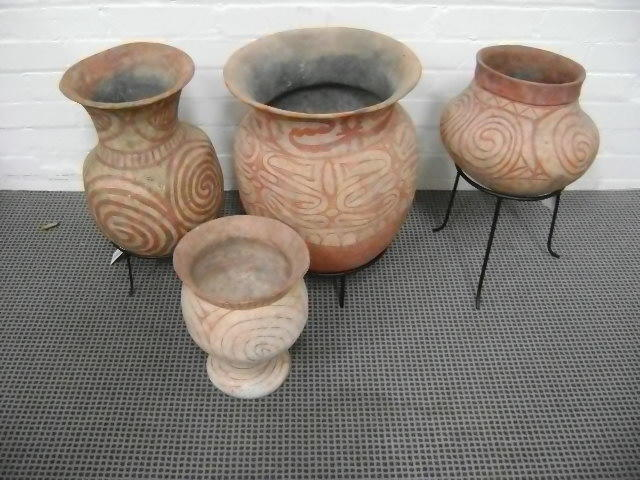 Four far Eastern terra cotta vases,with stylised linear decoration, three with wrought iron stands. (4)
