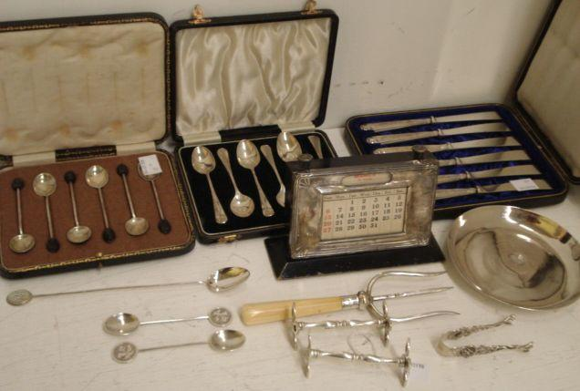 A cased set of six silver 'bean end' coffee spoons,cased set of four silver coffee spoons and a further pair, cased set of six silver handled tea knives, silver mounted perpetual calendar and photoframe, silver bread or ham fork, pair of silver knife rests, 1928, Indian foliate embossed silver bowl, seven metalware spoons, sugar tongs and an Egyptian circular dish.