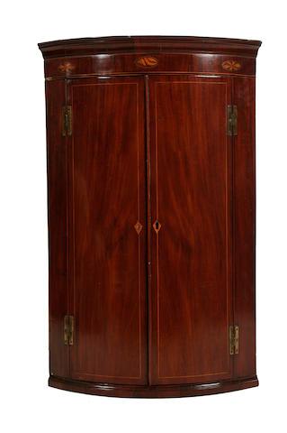 A George III mahogany hanging corner cupboard
