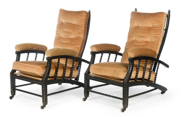 A pair of late 19th Century ebonised reclining easy armchairs of Aesthetic/Arts & Crafts style