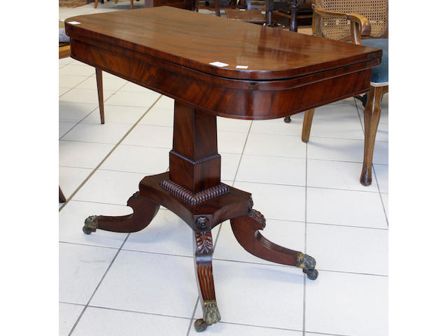 A late Regency mahogany card table, the hinged 'D' shape fold over top on a square tapering pillar with gadrooned collar, the concave sided platform on palmette headed reeded downswept quadripartite base, brass claw caps and castors.