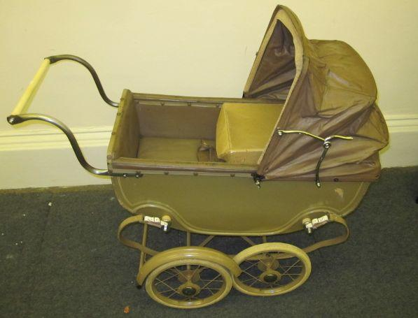 A dolls pram, circa 1940, by Star & Simcett Ltd, London, the coach built body in khaki paint with hood and cover, white rubber wheels together with an Edwardian child's tea set decorated in rose and ribbon swags.