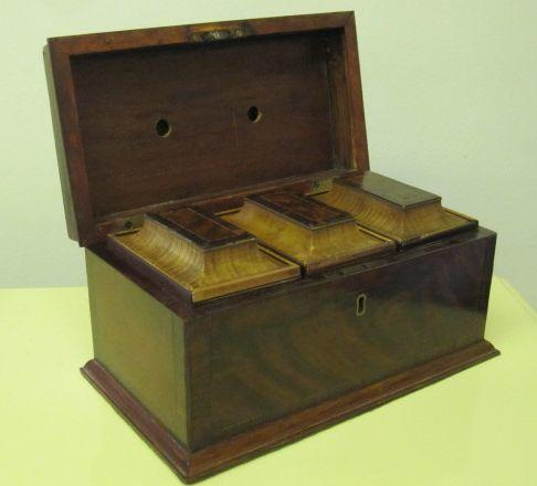 An 18th Century mahogany crossbanded tea caddy, the lift lid to reveal three slide top containers, together with a small mahogany slide top box with key and spoon. (2)
