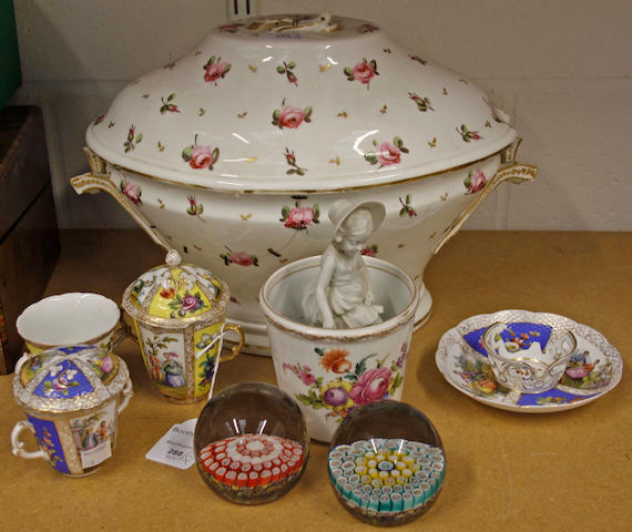 A Derby oval two handled soup tureen and cover, early 19th Century, painted with roses, red painted marks, bisque figure of a girl, two Dresden two handled chocolate cups and covers, a saucer, similar two handled cup, Dresden jardiniere decorated with floral bouquets and two glass paperweights. (9)