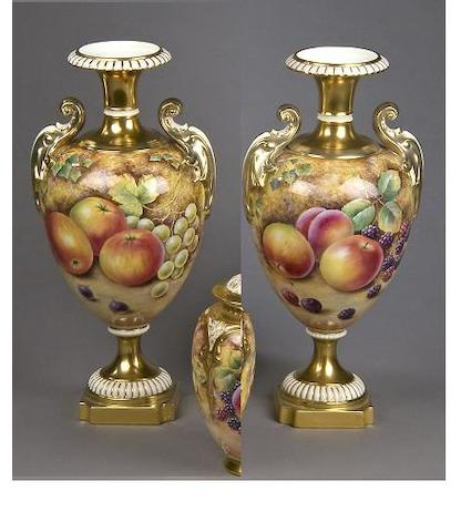 A pair of Royal Worcester twin handled urns signed David Fuller