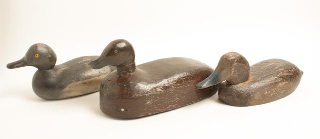 A group of three wooden duck decoys