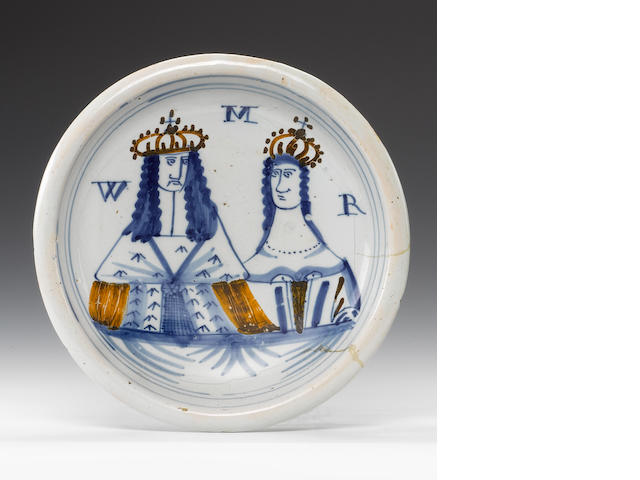 A London delftware portrait plate of William and Mary, in blue and ochre (damage on right hand side)