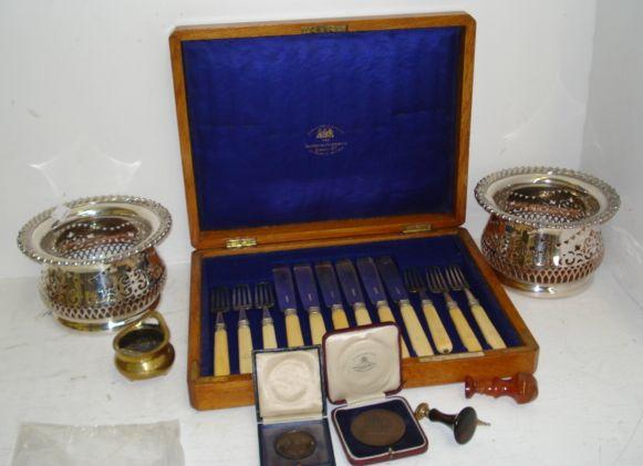 A pair of silver plated pierced bottle holders, a small polished bronze censur, a polished cornelian desk seal, another, with polished wood handle, a fob seal with foiled back stone, three cast brass Dickensian figural pipe tampers, nine various cased silver and bronze Honorable Artillery Company medals, and an oak cased set of six each ivory handled fish eaters.
