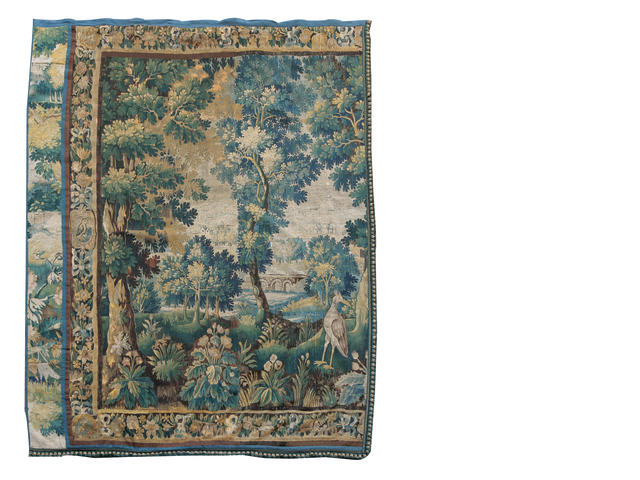 A Flemish 18th century Verdure tapestry cut in two, to form a pair