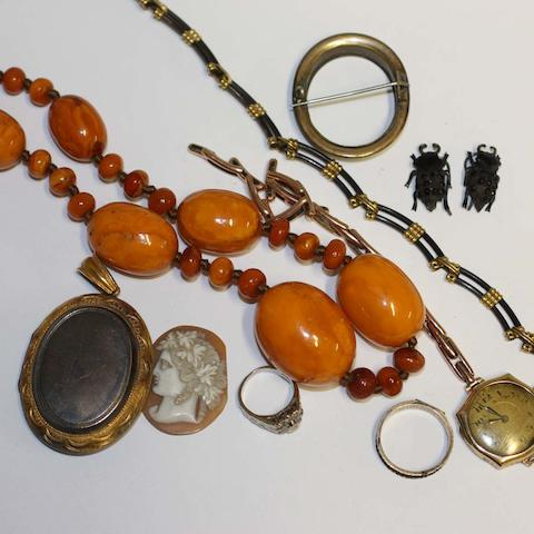 A Victorian gilt metal oval locket, engraved detail, a 20th Century cluster ring set with eight single diamonds, one lacking, an elephant hair necklet with reeded mounts, a 19th Century hair set mourning ring a string of polished amber beads, a lady's gold cased wrist watch on expandable strap (a/f), a carved shell cameo set brooch and an unusual 'French jet' earrings, in the form of beetles.