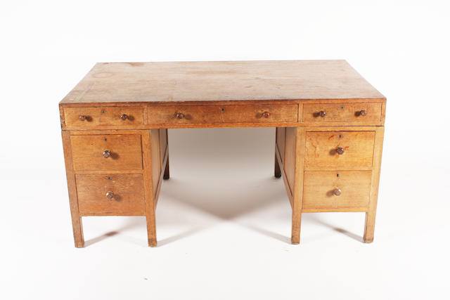 An oak twin pedestal desk attributed to Heal's