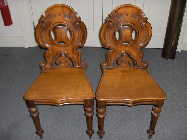 A pair of Victorian carved oak hall chairs on turned front legs