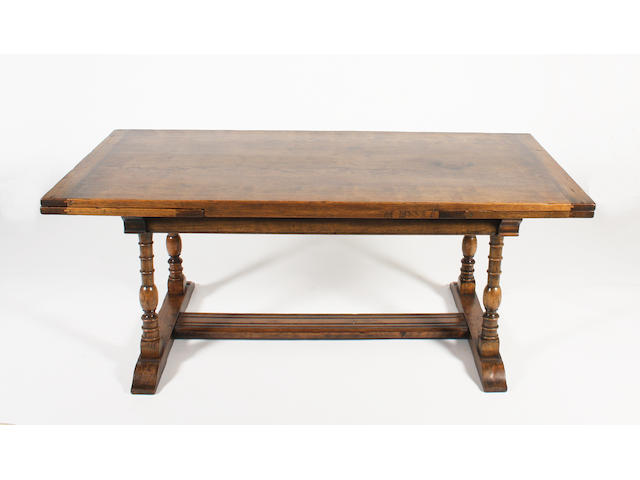 A reproduction, 17th century style,  stained oak draw-leaf dining table, by Frederick Tibbenham