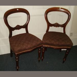 A set of six Victorian mahogany balloon back dining chairs,with stuff-over seats, on turned legs.