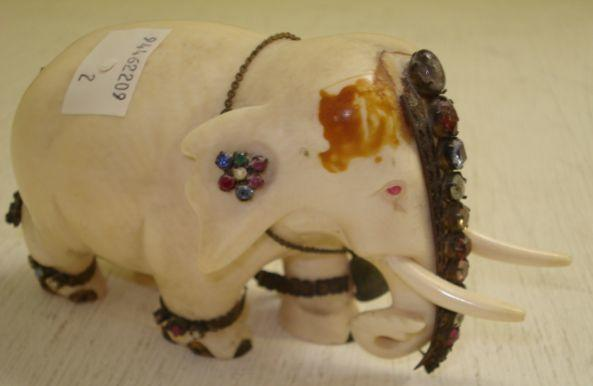 A carved ivory elephant, the standing animal with stone set leg bands and head dress,12cm.
